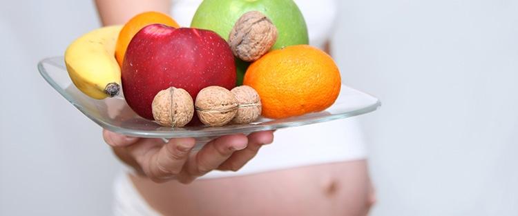 tehotná žena drží misu s ovocím a orechami – lejdy.sk